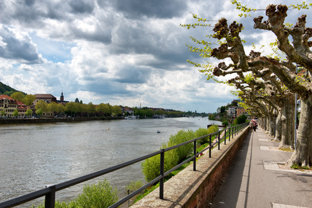 philosophers: Philosophers Walk Tree-Lined Waterfront Trail on Bank of Neckar River with View of Old Town at Heidelberg, Baden-Wurttemberg, Germany with Overhead Cloudy Sky Stock Photo