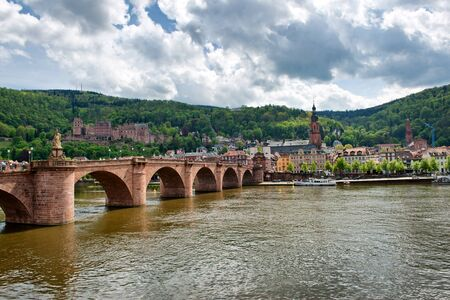 old bridge: View of Historic Old Bridge Crossing Neckar River to Old Town Heidelberg, Baden-Wurttemberg, Germany on River Bank Below Lush Green Foothills Stock Photo
