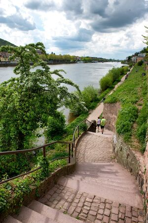 bordered: Couple Walking Along Riverfront Trail Bordered by Green Foliage on Bank of Neckar River, Heidelberg, Baden-Wurttemberg, Germany