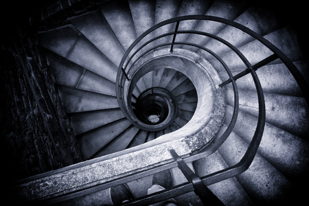 Black and White High Angle View of Spiral Staircase Winding Downward in Historical Building, Looking Down at Bottom of Stairs in Elegant Old Building