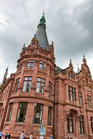 architectural exterior: Architectural Exterior of Corner Tower of Heidelberg University Library Underneath Grey Rain Clouds, Baden-Wurttemberg, Germany
