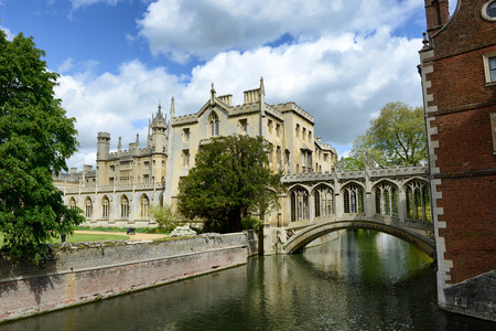 cambridge: St Johns College, Cambridge University, and the Bridge of Sighs over the River Cam in Cambridge, England in a scenic landscape view under a cloudy blue sky
