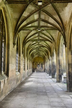 paved: Covered paved stone walkway with Gothic arches receding into the distance and arched windows and portals to the exterior