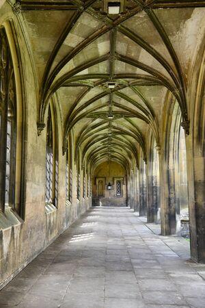 empedrado: Cubierto calzada de piedra pavimentado con arcos góticos retroceso en la distancia y ventanas de arco y portales en el exterior