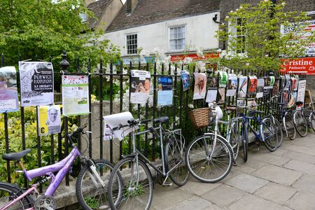 locked up: Row of Bicycles Locked Up Along Iron Fence Covered with Advertisement Posters, Cambridge, England Editorial