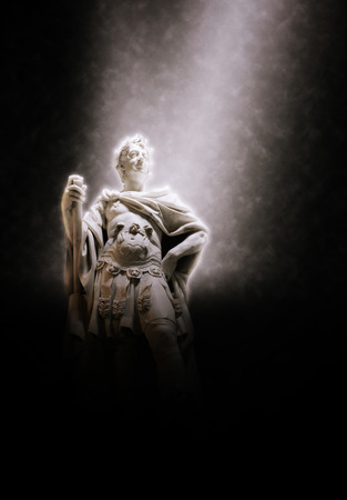 Stone Statue of Triumphant and Powerful Looking Julius Caesar Dramatically Lit by Above Spotlight on Dark Background