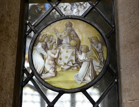 ecclesiastical: Close Up of Religious Themed Artwork Embedded in Window - Architectural Detail of Spiritual Worship Circular Artwork at Kings College, University of Cambridge, England Editorial