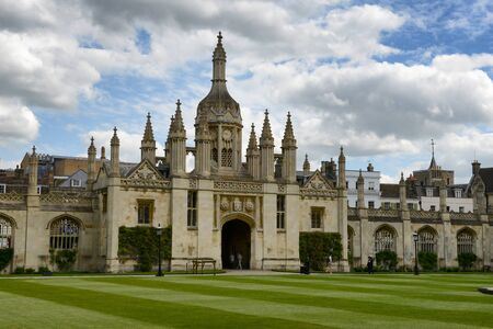 gatehouse: Kings College Gatehouse and Gothic Clock Tower as seen from Inside Courtyard with Manicured Green Lawn, University of Cambridge, England