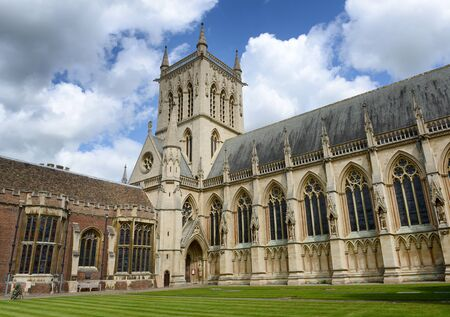 gilbert: Exterior and Entrance of St Johns College Chapel, Designed by Sir George Gilbert Scott in 1861, with Green Inner Courtyard and Blue Sky with White Clouds, University of Cambridge, England Editorial