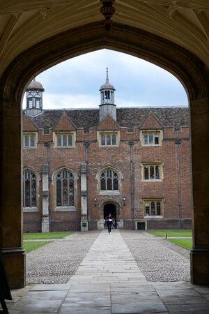 punting: View of Stone Path Through Archway to Historic Brick Building on Interior of Courtyard on Grounds of St Johns College, University of Cambridge, England