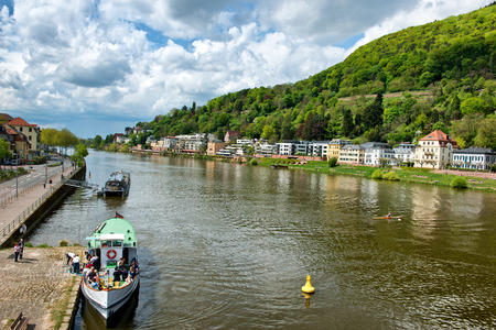 hillsides: Tour Boats and Buildings on River Banks of Neckar River, Heidelberg, Baden-Wurttemberg, Germany Framed by Lush Green Hillsides