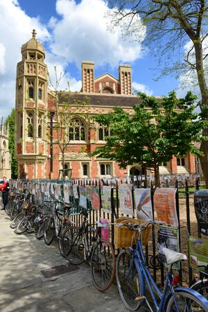 bordering: Row of bicycles parked on the sidewalk along a wrought iron fence bordering an urban street in Cambridge, England with advertising posters on the railing and an historic building in the background