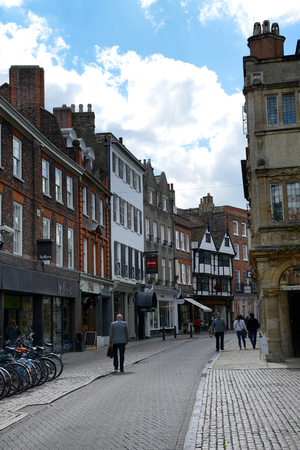 recedes: Pedestrians Walking on Narrow Cobblestone Street Lined with Quaint Low Rise Buildings, Cambridge, England Editorial