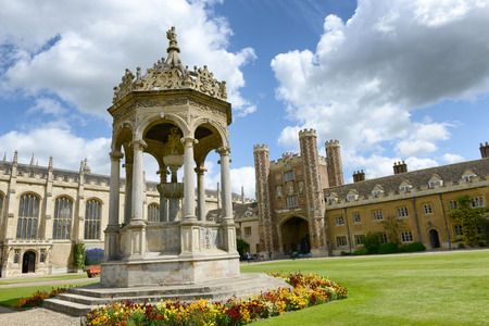 Ornate stone fountain in the Great Court at Trinity College, Cambridge University, Cambridge, UK standig in manicured lawns with the Great Gate visible behind Redactioneel