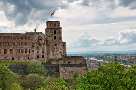 Historic Ruins of Heidelberg Castle with Waving Flag Overlooking Picturesque Town and Neckar River Below, Baden-Wurttemberg, Germany photo