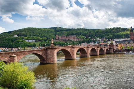 nestled: Old Bridge Over Neckar River with View of Old Town Heidelberg, Baden-Wurttemberg, Germany Nestled in Lush Green Foothills on River Bank