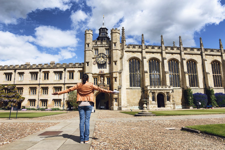 Young woman or student standing facing the Kings Gate and chapel, Trinity College, Cambridge University, Cambridge, UK with her arms outspread in the center of the Great Court Sajtókép