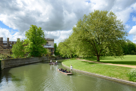 punting: People punting on the river in Cambridge rowing away from the camera around a bend in the river past historical buildings amongst lush green trees