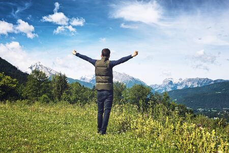 arm outstretched: Man rejoicing with his arms outstretched as he stands on a plateau overlooking the Alps in the Berchtesgaden National Park, Germany