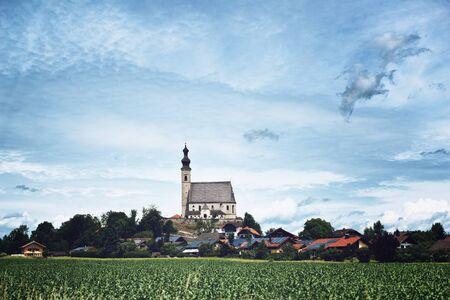 IGLESIA: Iglesia eleva sobre Red Roof Casas en tradicional aldea rural en Baviera, Alemania Rodeado de Campo Verde