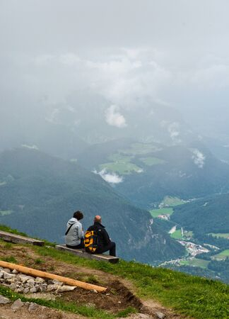 viewpoints: Couple of hikers wearing backpacks sitting on benches at a mountain lookout enjoying the alpine view with a lush Bavarian valley shrouded in mist below them