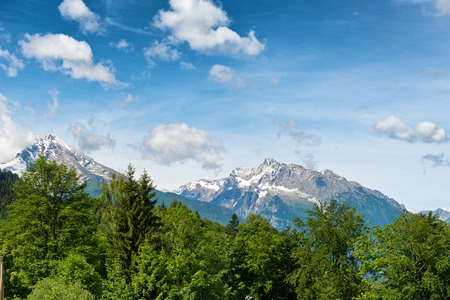berchtesgaden: Snow-capped alpine peaks in the Berchtesgaden National Park, Bavaria, Germany in a scenic landscape under a cloudy blue sky