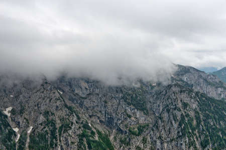 inclement: Close up of rocky mountain outcrop partially obscured by low hanging cloud Stock Photo
