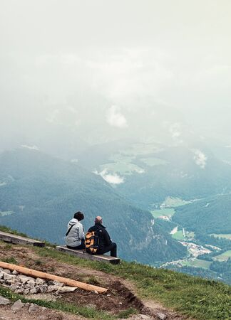 obscuring: Rear view of two hikers sitting on a piece of wood looking down at a magnificent scenic view of a valley, cloudy mist partially obscuring view Stock Photo