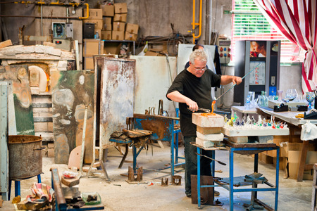 gaffer: BARCELONA, SPAIN - MAY 03: Glass maker on his workplace in Poble Espanyol, Barcelona, Spain on May 03, 2015