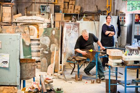 molted: BARCELONA, SPAIN - MAY 03: Glass maker on his workplace in Poble Espanyol, Barcelona, Spain on May 03, 2015