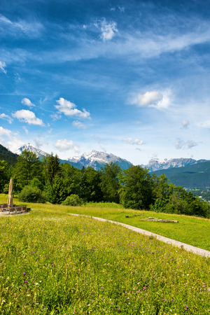 distance: Footpath in the Berchtesgaden Alps in Germany crossing a lush green grassy plateau with a view to distant mountain peaks