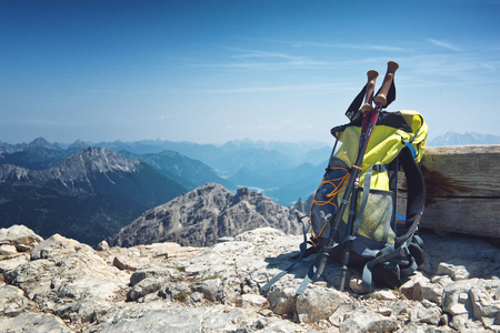 summits: Backpack or rucksack balanced against a rock on top of a mountain summit in the Alps, Hochvogel, Germany, conceptual of a healthy, active outdoor lifestyle and sport