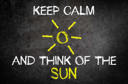 unwinding: Keep Calm and Think of the Sun Message for Summer Vacation Concept Written on Blackboard with Glowing Sun Drawing.