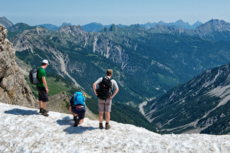 valley below: HOCHVOGEL, GERMANY - 05 JULY: Climbers on top of the Kalter Winkel upfold, looking over a rocky ledge at the mountain ranges and valley below, view from behind at Hochvogel, Germany on May 05, 2015