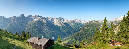 forested: Rustic log cabins on an Alpine plateau near Hochvogel, Germany, overlooking a scenic panorama of forested slopes and rugged mountain peaks