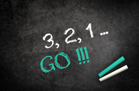 go to: Counting down to Go concept with a handwritten countdown 1, 2, 3, and GO on a chalkboard in green and white letters with sticks of chalk Stock Photo