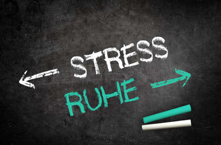 destress: Conceptual Stress and Silence Message Written on a Black Chalkboard with Chalk Sticks in the Lower Right Corner. Stock Photo