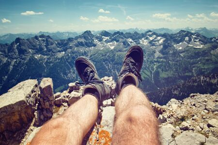 personal perspective: Climber in hiking boots on a rocky ledge overlooking the peaks of the Alps at Hochvogel, Germany, personal perspective looking down his legs to the view