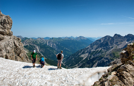 ledge: HOCHVOGEL, GERMANY - 05 JULY: Climbers on top of the Kalter Winkel upfold, looking over a rocky ledge at the mountain ranges and valley below, view from behind at Hochvogel, Germany on May 05, 2015