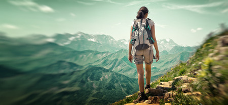trails: Woman hiking in mountain range. Rear view of a female backpacker walking on a small foot path in a mountain landscape. Image for trekking, hiking or climbing.