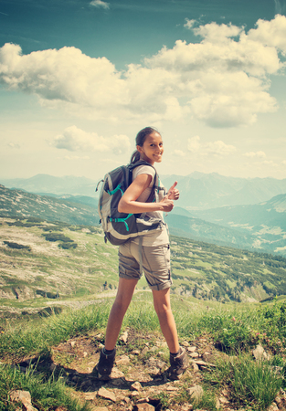 Woman hiking in mountain range. Rear view of a female backpacker doing thumbs up in a mountain landscape. Image for trekking, hiking or climbing. Stock Photo