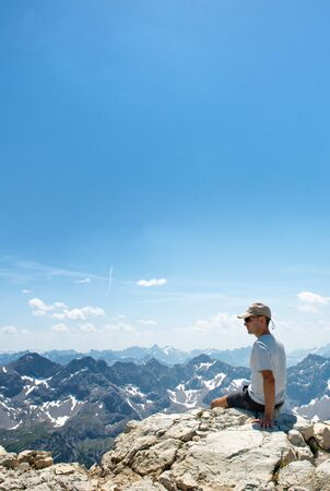 allgau: Rear view of hiker at the top of a rock on the Hochvogel mountain summit enjoying the sun and fantastic mountainous surrounding and wild nature. With Copyspace on blue sky.