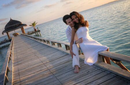 summer dress: Happy loving couple in white clothes posing on a pier on Maldives