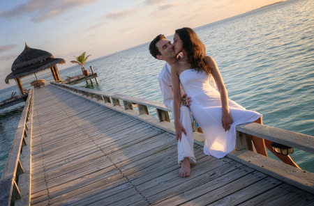 fondle: Happy loving couple in white clothes kissing on a pier on Maldives