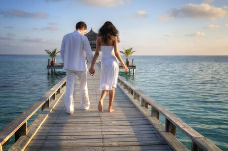 couple relaxing: Happy loving couple in white clothes walking on a pier on Maldives