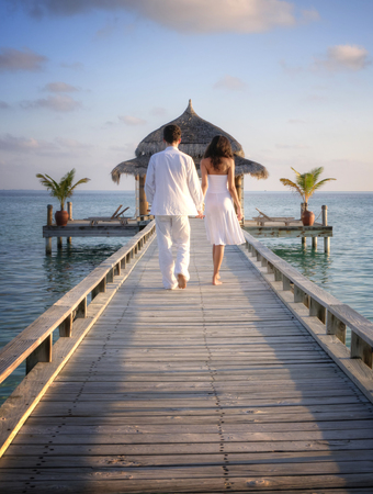 indian ocean: Happy loving couple in white clothes walking on a pier on Maldives
