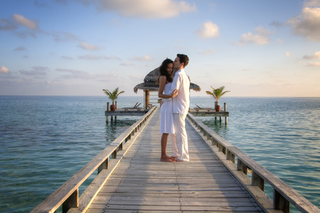 beach kiss: Happy loving couple posing in white clothes on a pier