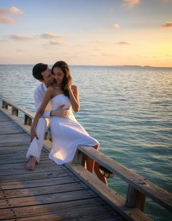 parejas sensuales: Pareja amorosa feliz en la ropa blanca que presenta en un muelle en las Maldivas