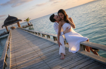 romantic beach: Happy loving couple in white clothes posing on a pier on Maldives
