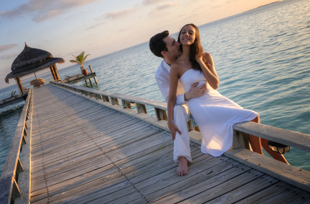 young couple kiss: Happy loving couple in white clothes posing on a pier on Maldives